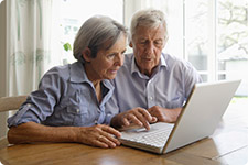 Mature couple interacting with laptop computer.