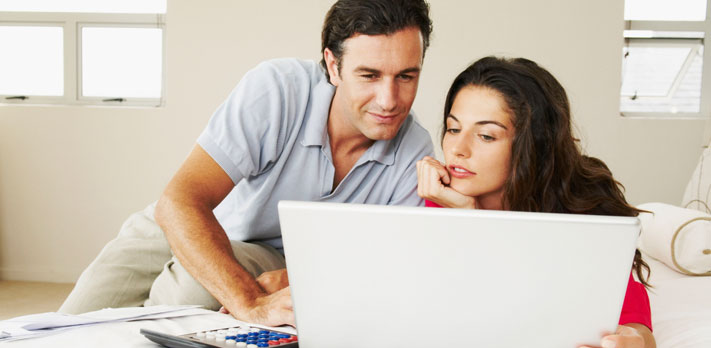 Persons interact with laptop computer.