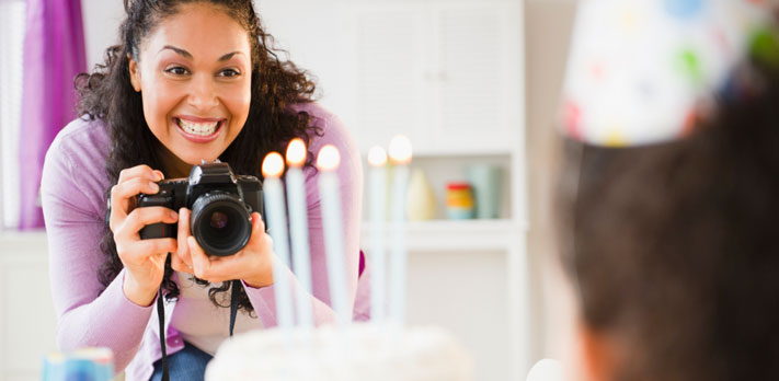 Woman takes pictures at birthday party.