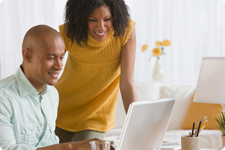 Couple interact with laptop computer.